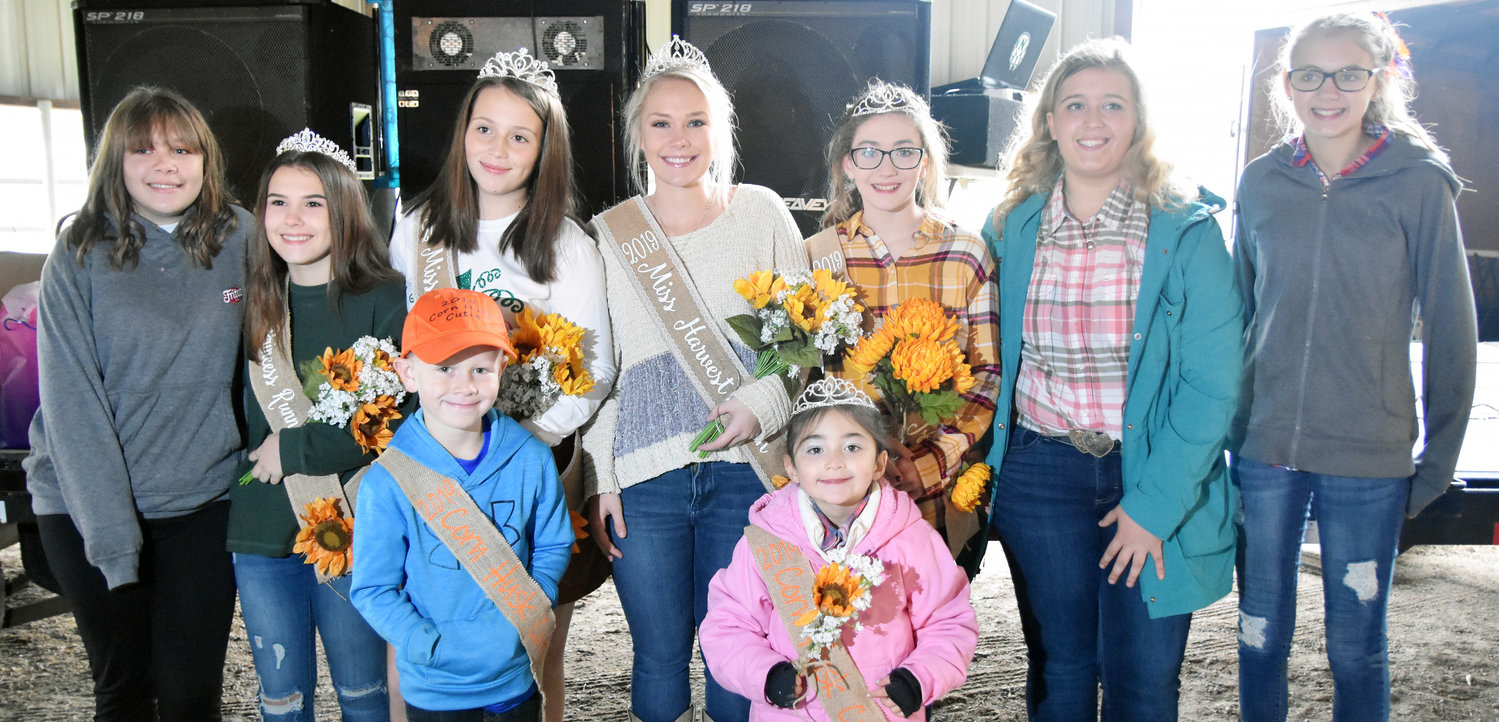 Belle Harvest Festival attendees did not let cold rainy weather stop them from have a fun filled day. The festival was moved from downtown to the shelter of the sale barn at the city park. Large crowds gathered  to watch the Dance teams, crowning of the queens and shop at the many venders. Corn Husk Cutie winners where Maddix Devine and Jaelyn Perkins (front from left). Trinidi Medlock, Princess First Runner-up Hilah Drewel, Princess Ryleigh Long, Queen Mya Honse, Jr. Princess Savannah Perkins, Alexis Bacon and Alexis Kirby. See more on page 5.