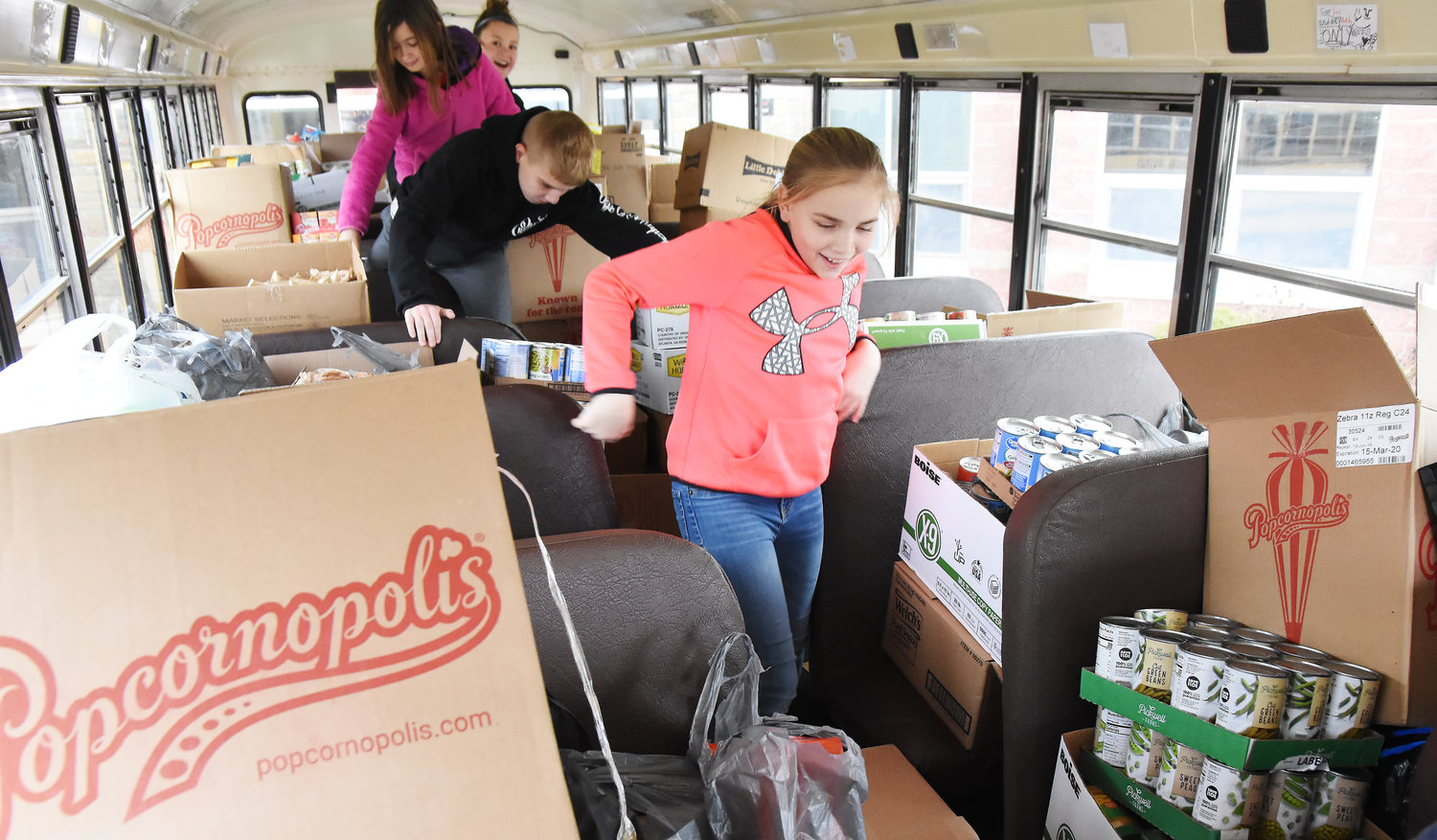 Owensville elementary School students (front to back) Rylee Dare, Wyatt Lewis, Hannah Coello, and Joleen Braun climb out of the bus Monday after finding themselves packed in with food stocks collected by students in their school.