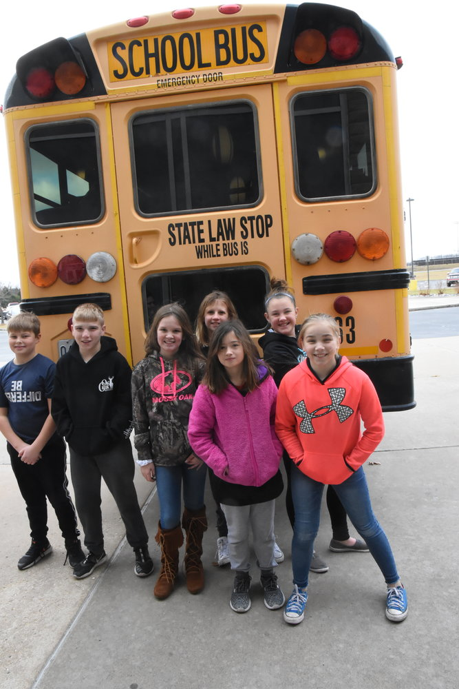 "Students stand behind the bus that is filled with ""Fill the Bus"" donations."