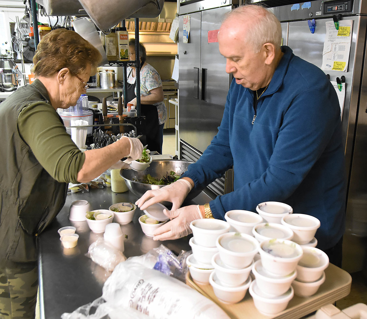 OWENSVILLE Senior Center staff member Judy Cain and Bob Niebruegge, a board of directors member for Aging Best, prepare salads for curbside meal delivery on Friday.