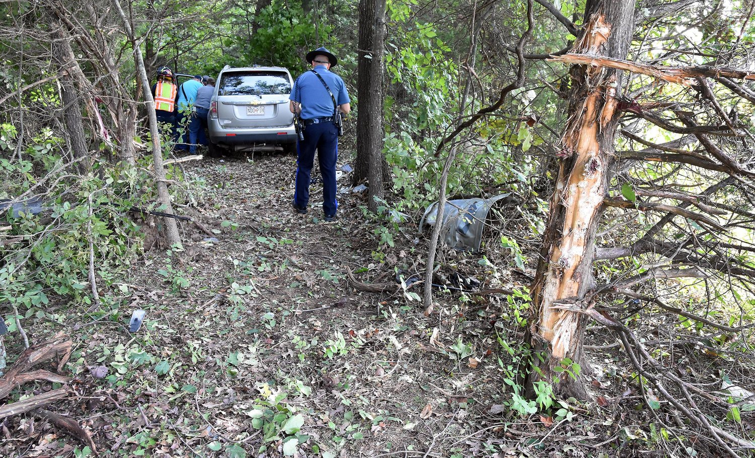 MSHP TROOPER B.R. Lange collects information for a crash report Friday morning after an Owensville woman veered off Highway 28 and came to a stop about 30 feet into the wood line. Firemen from Bland and Owensville had to remove several small trees to access the site and extricate her from her car. Her car careened off a large cedar (right) but missed the oak beside Lange.