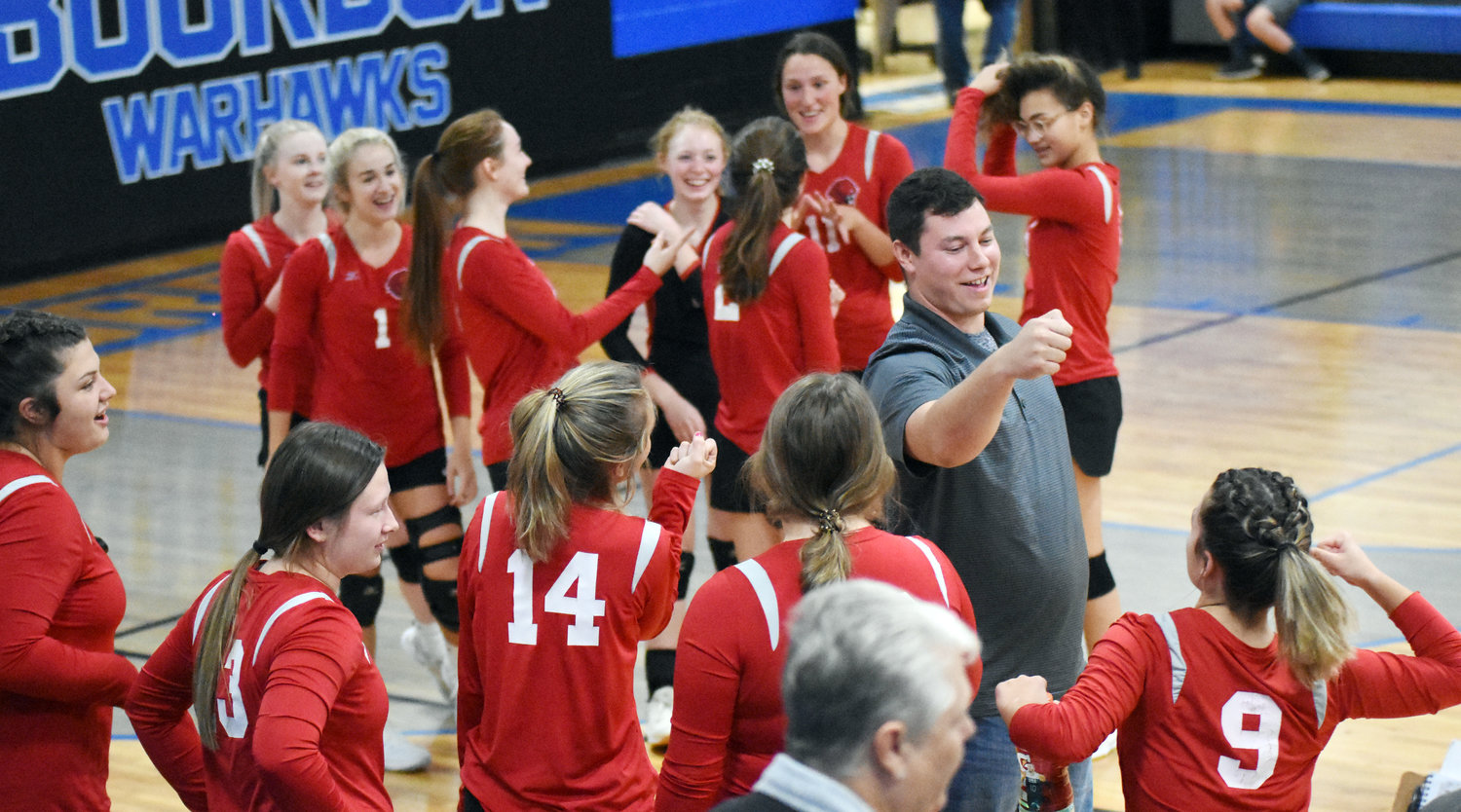 Lady Tiger volleyball coach Evin Farris (above, center) fist bumps Mea Jones (9) while celebrating Belle's first district championship since 2003 following their victory in three sets last Tuesday over Linn in the MSHSAA Class 2, District 7 championship match.