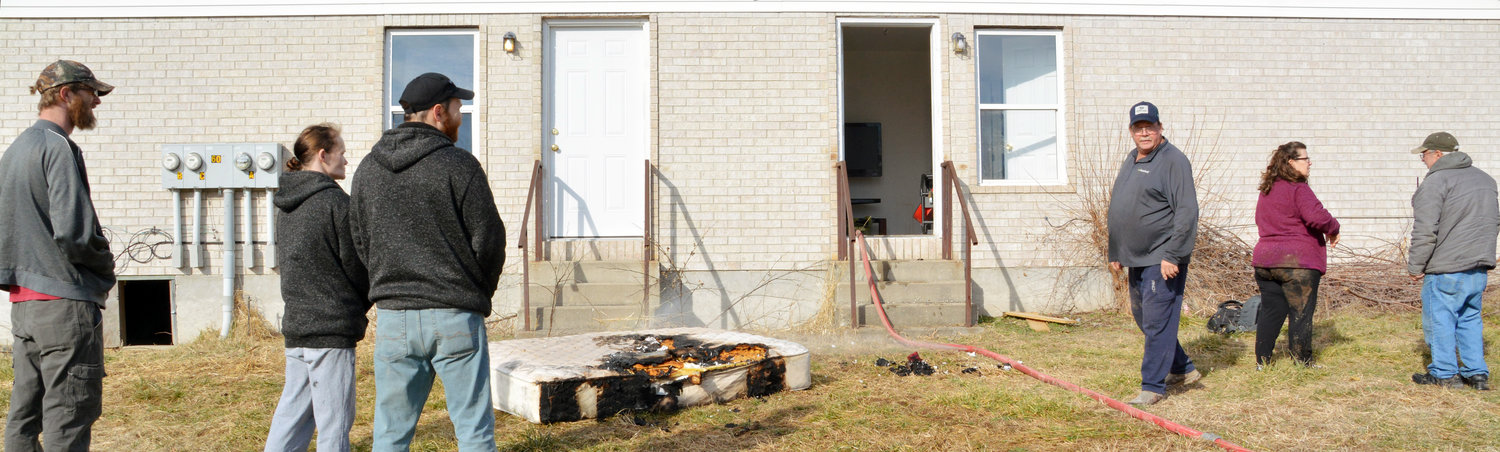 Neighbors and family members stand outside the Belle apartment of Corbin Forsee and Alexis Mayer that caught fire on Jan. 29. Forsee's parents, Marty and Cheryl stand to the right of the entryway, assessing the situation to see what help is needed.