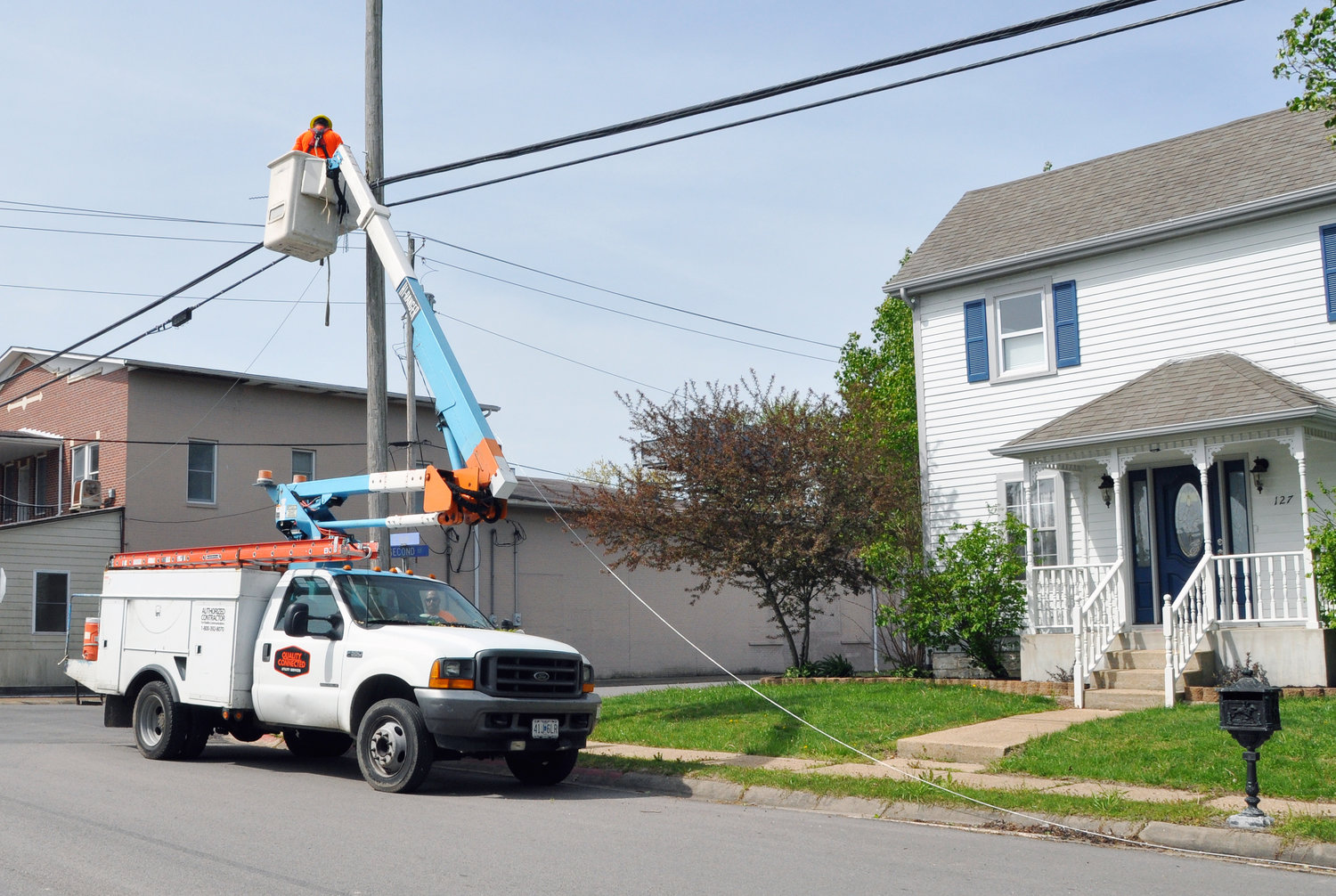 Contractors with Fidelity Communications were found on Main Street at Second Street Monday morning doing preliminary work to run fiber optic cable to residents of Gerald. The crew was running a metal cable above the street (above) upon which the fiber optic cable will be wrapped.